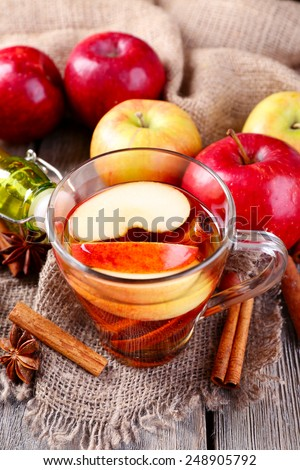 Apple cider with cinnamon sticks, spices and fresh apples on wooden background - stock photo