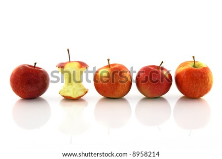 Apple core among whole apples, reflecting on white background.