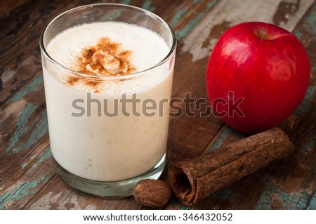 Apple crumble smoothie milkshake topped with cinnamon and nutmeg spices. Served on a rustic wooden table.