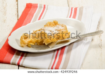 apple crumble with powdered sugar on oval plate and fork - stock photo