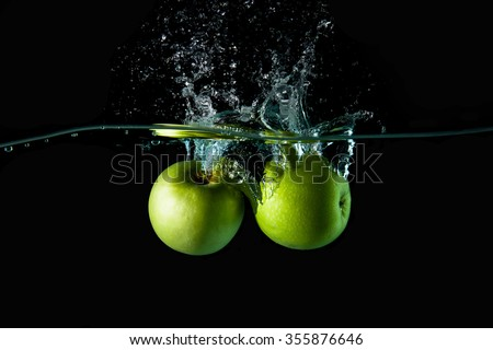Apple dropping into water on black background ,Apple falls deeply under water,Apple in water on a black background. - stock photo