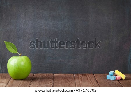 Apple fruit and chalks on classroom table in front of blackboard. View with copy space - stock photo