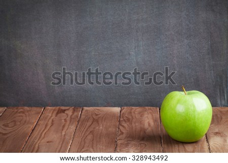 Apple fruit on classroom table in front of blackboard. View with copy space - stock photo