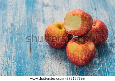 Apple has four children bite stacked right on wood floor blue and white. - stock photo