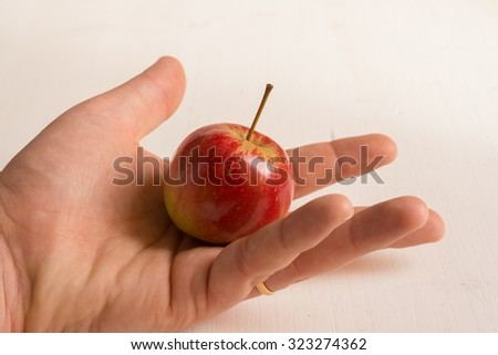 apple held in hand in front of white background