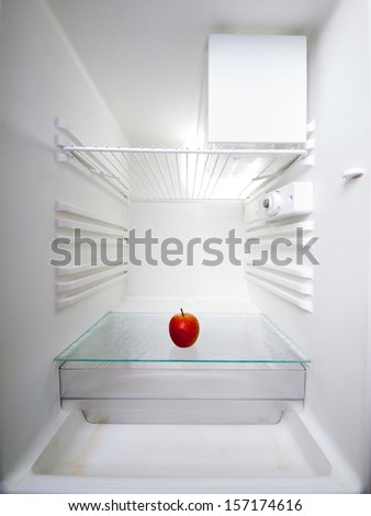 apple in an empty refrigerator - stock photo