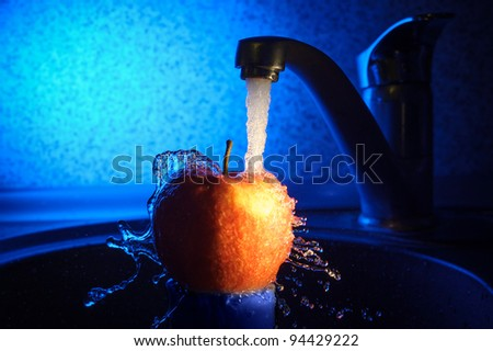 Apple in water stream - stock photo