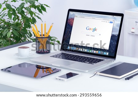 Apple 15 inch MacBook Pro Retina with an open tab in Safari browser which shows Google search web page with iPad and iPhone on the office desk workplace. Varna, Bulgaria - May 29, 2015. - stock photo