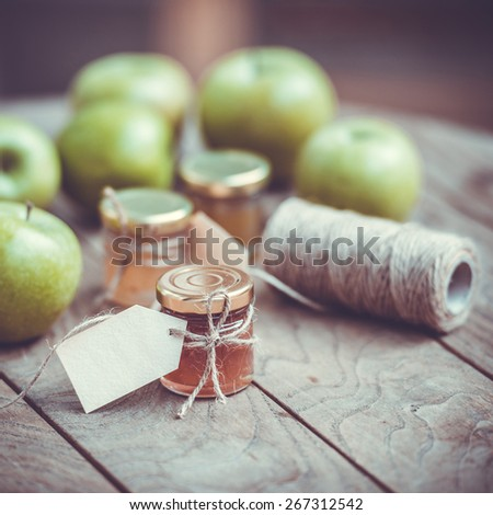 Apple jam in a small glass jar and green apples on wooden table. Blank label provides copy space for a message. Toned image - stock photo