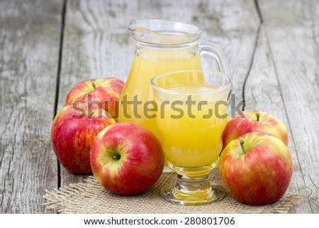Apple juice and apples on wooden background - stock photo