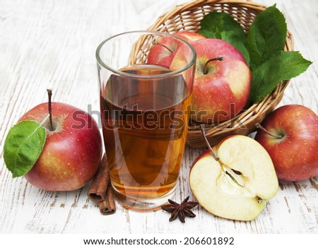 Apple juice and fresh apples on a wooden background - stock photo