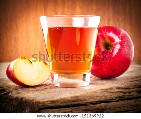 Apple juice. Fresh organic ripe apples and glass of juice on old wooden table background. Image in vintage style - stock photo