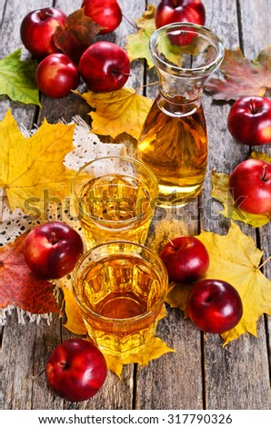 Apple juice in a transparent glass on a wooden surface on a background of red apples and maple leaves - stock photo