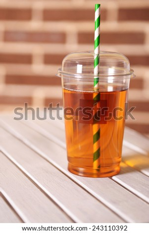 Apple juice in fast food closed cup with tube on wooden table and brick wall background - stock photo