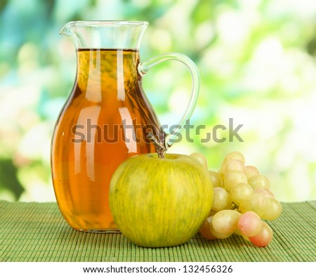 Apple juice in pitcher on table on bright background - stock photo
