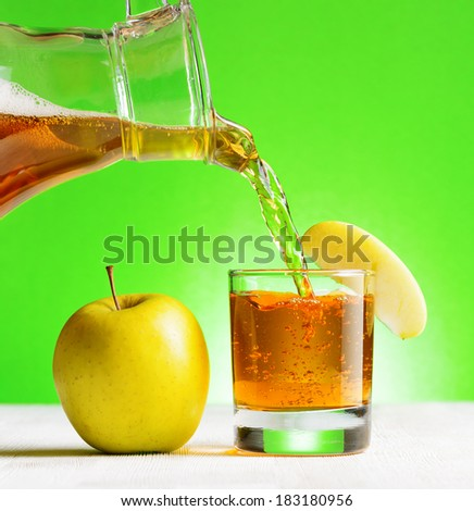 Apple juice pouring from jug into a glass. Green background. - stock photo