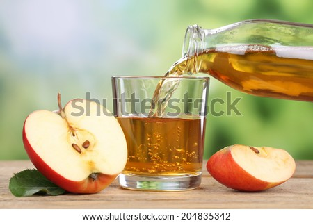 Apple juice pouring from red apples fruits in summer into a glass - stock photo