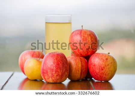 apple juice with apples on a wooden table, outdoor - stock photo