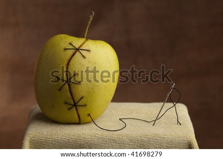 apple manipulated fruit with thread holding it together genetically modified food gmo concept