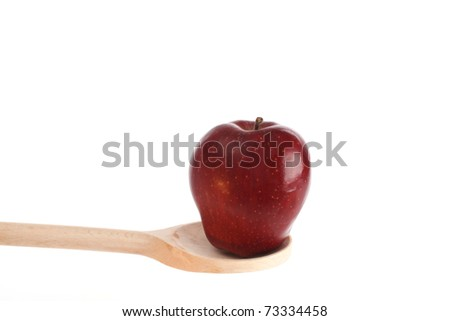 Apple on a wooden spoon isolated against a white background