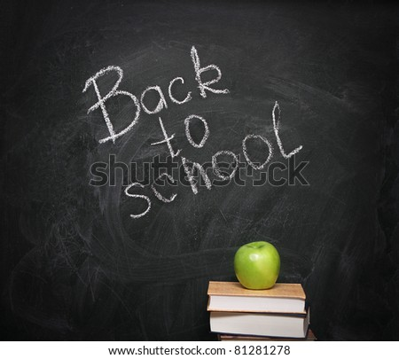 Apple on books against blackboard with text - stock photo
