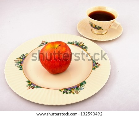 Apple on fine china plate with coffee tea isolated white background - stock photo