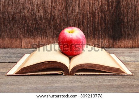 Apple on old book with wooden background.