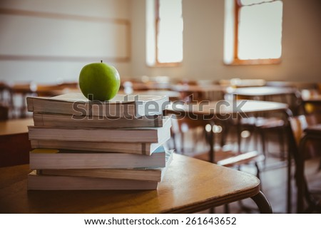 Apple on pile of books at the elementary school - stock photo