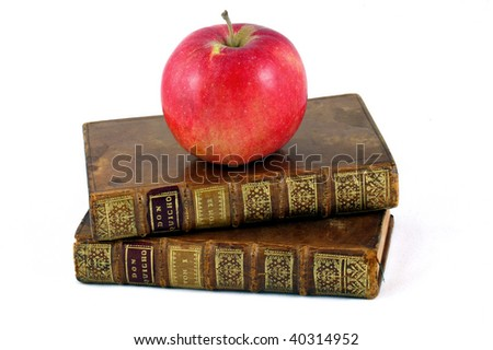 Apple on top of two books symbolizing knowledge or learning - stock photo