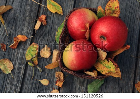 Apple on wooden table with fallen autumn leaves