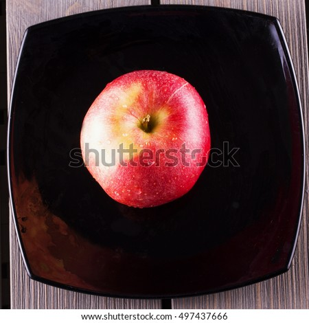 Apple over black plate, seen from above, square image