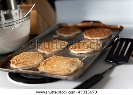 Apple pancakes cooking on the hot stove griddle.  Shallow depth of field. - stock photo