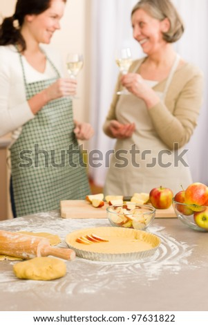 Apple pie baking two women drink wine together in kitchen - stock photo