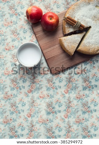 Apple pie on a wooden board with a mug of milk. Juicy and ripe apples. Top view. - stock photo