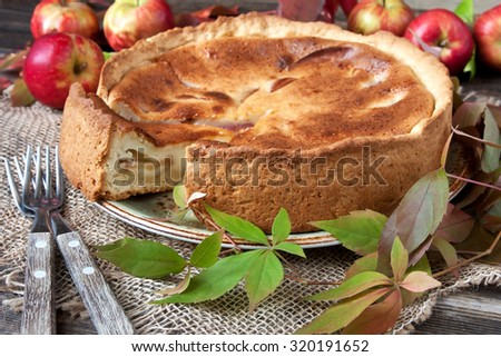 Apple pie on the wooden table with fresh apples  - stock photo