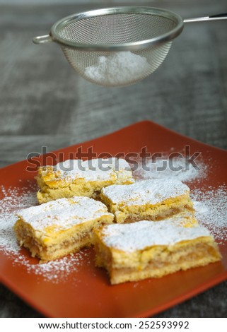 Apple pie - pouring sugar on it - stock photo