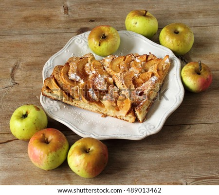 Apple pie sharlotka pieces on white bone plate with apples on wooden vintage table closeup