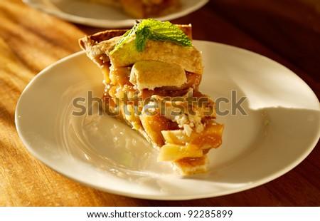 apple pie with mint garnish. - stock photo