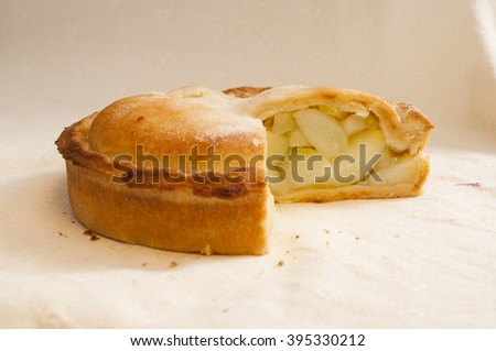 Apple pie with slice missing on white cloth.