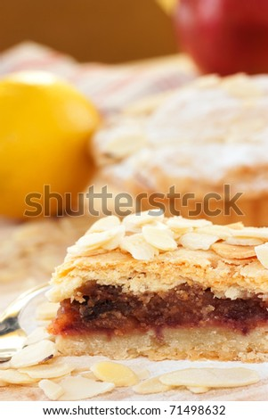 Apple pie with sprinkled peeled almonds and apple in the back