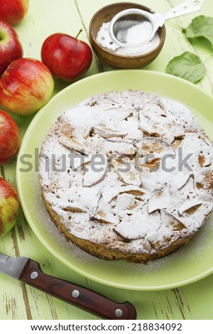 Apple pie with sugar powder and red apples on a wooden table