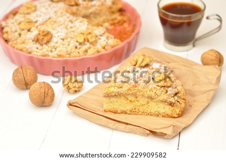 Apple pie with walnuts and powdered sugar in a ceramic lilac form, a cup of coffee on a white wooden background - stock photo