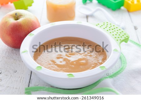 Apple puree in bowl  on white table - stock photo