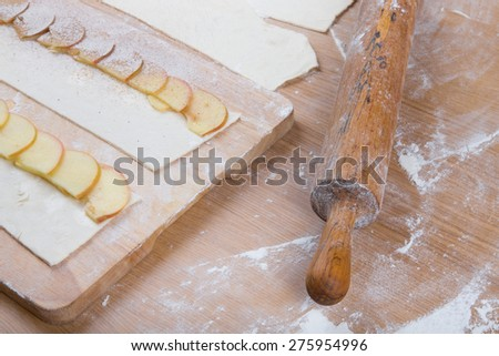 Apple slices on stripes of dough and rolling pin on a light wooden table with flour. - stock photo