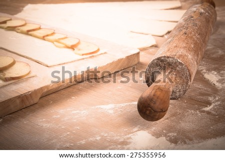 Apple slices on stripes of dough and rolling pin on a light wooden table with flour. Toned. - stock photo