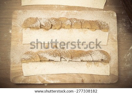 Apple slices on stripes of dough on a light wooden table with flour. Toned. - stock photo