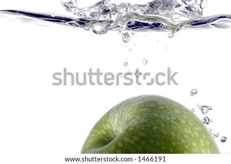 apple splashing into water - stock photo