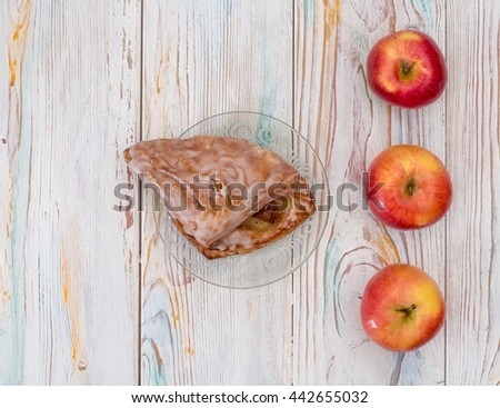 Apple strudel is a white wooden table next to a red apple - stock photo
