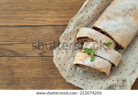 Apple strudel on wooden background. - stock photo