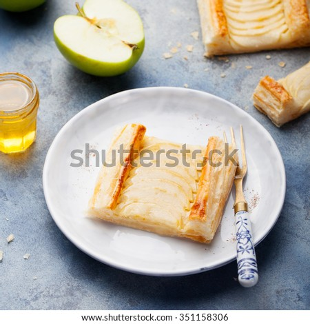 Apple tart, puff pastry strips with vanilla custard on a stone background